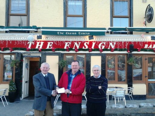 Mick Coakley, winner of Shamrocks Lotto Jackpot, receives his cheque outside the Ensign Bar from John Towmey (Treasurer) and Paddy Andrews (winning ticket seller).